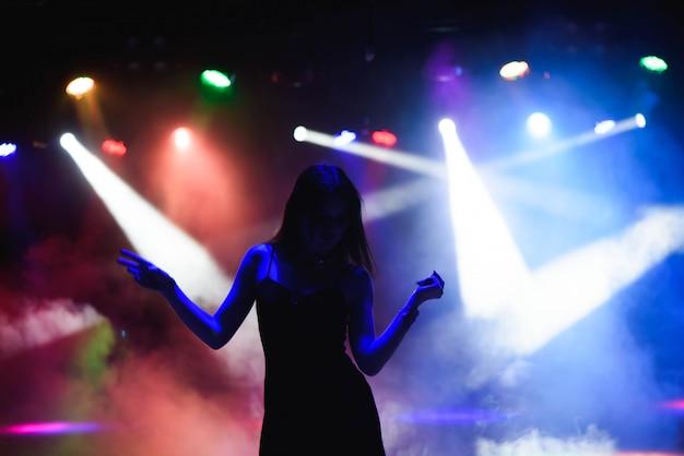 Танцующий силуэт девушки в ночном клубе