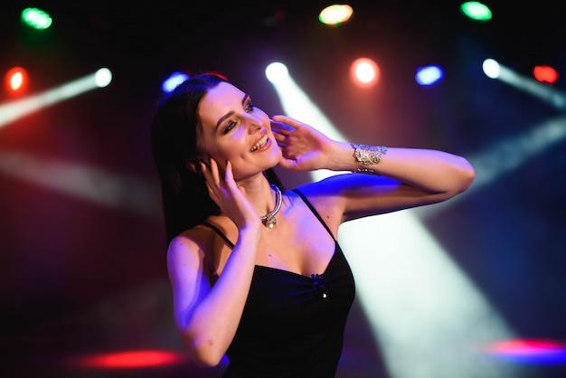 Красивая сексуальная женщина на фоне цветных ламп.