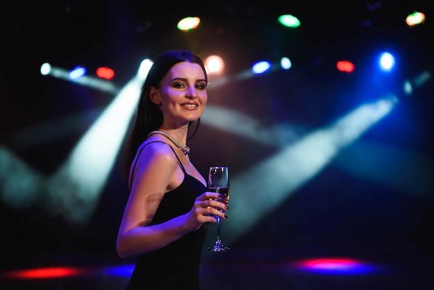 Молодая женщина празднует черное платье, держа бокал шампанского. вечеринка.