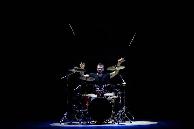 キャップのドラマーとヘッドフォンが煙の中で白い光の下でコンサートでドラムを演奏します。