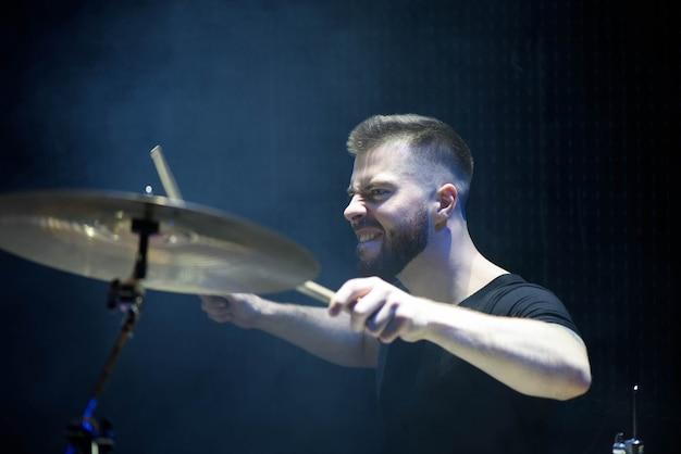 Барабанщик в кепке и наушниках играет на барабанах на концерте под белым светом в дыму
