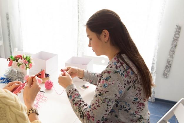 編みレッスンの若い魅力的な女の子