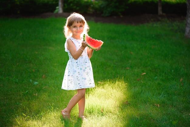 スイカを食べるとピクニックを楽しむかわいい女の子
