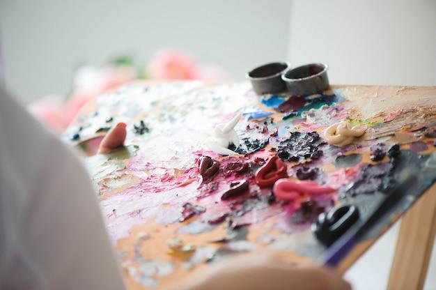 女の子アーティストがパレットに油絵の具を混ぜます