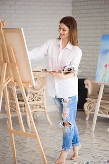 Женщина рисует картину на холсте масляными красками в своей студии