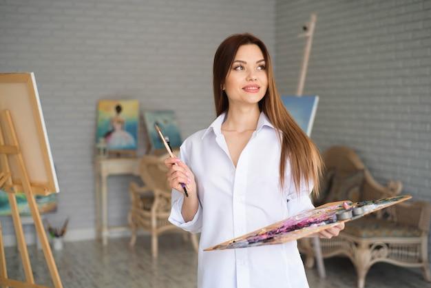 Молодая художница рисует картину в студии
