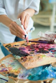 Искусство, творчество и люди концепции - крупным планом художника с мастихином натюрморт на мольберте в студии