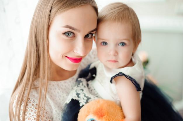 Мама обнимает и целует свою маленькую дочь