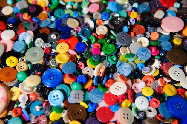 カラフルなプラスチック製の服のボタンがたくさん。多くの小さな丸ビンタ