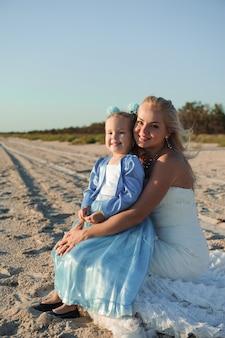 ビーチで彼女の娘と一緒にウェディングドレスで幸せな母