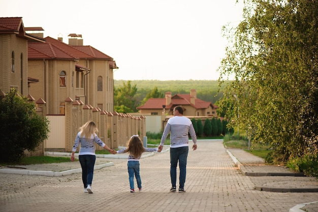 夏の時間を歩いて楽しんでいる少女と幸せな妊娠中の家族。