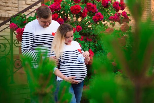 屋外で夫と若い妊婦。