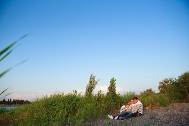 川のそばに座って彼女の家族と一緒に美しい妊婦。