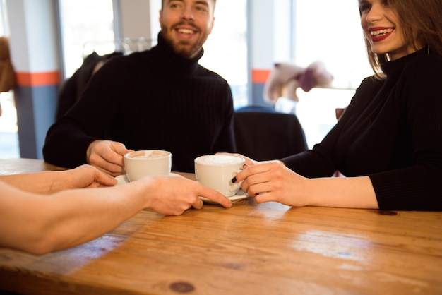 Дружественный бармен, предлагающий кофе эспрессо клиентам в интерьере современной кофейни.