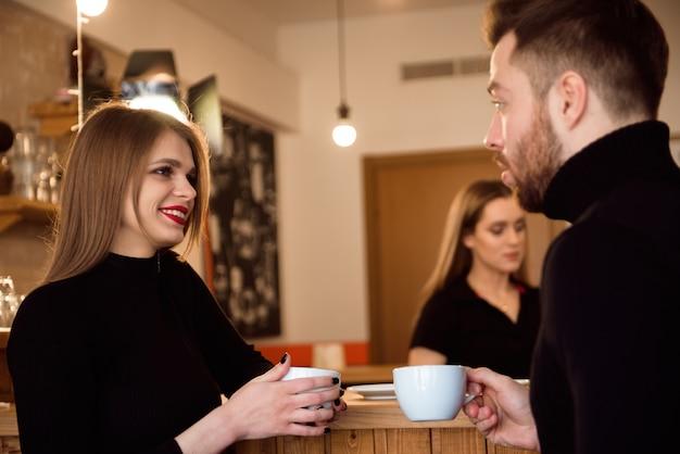 美しい女性とハンサムな男がコーヒーショップで時間を過ごしながらコーヒーを飲みます。