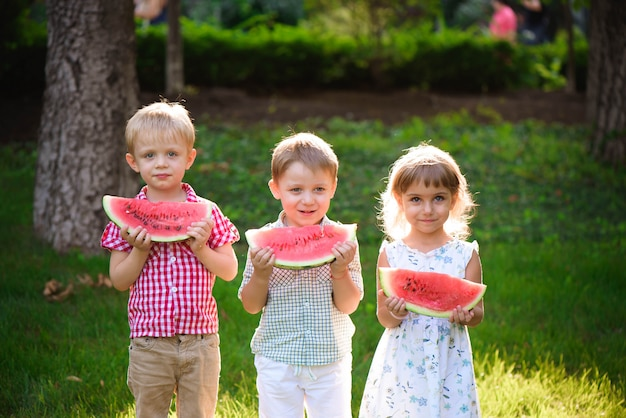 夏の公園で屋外でスイカを食べる面白い子供たち。