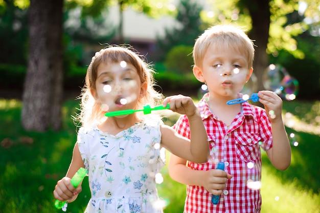子供と友人は日没で遊び場でバブルを再生します