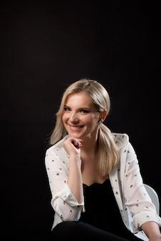 Молодой представлять бизнес-леди изолированный над черной предпосылкой стены сидя на стуле.