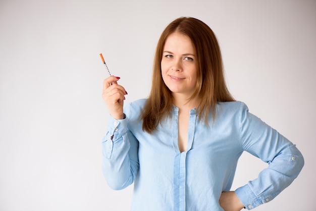 Женщина при шприц инсулина изолированный на белой концепции предпосылки диабета.