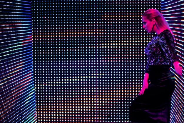 Модельная женщина в неоновом свете. арт дизайн женских диско танцоров, позирующих в ультрафиолете.
