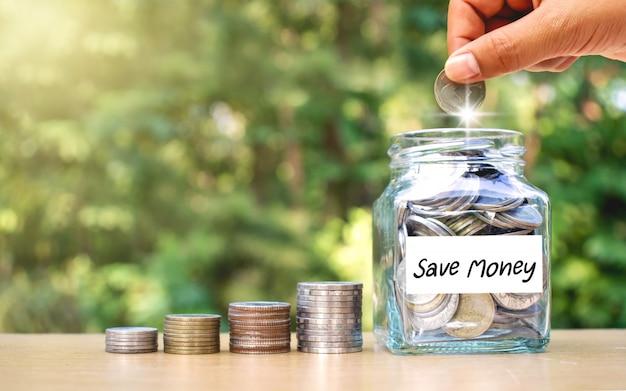 手はお金の瓶にお金を入れています。節約のアイデア。