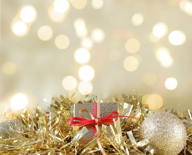 Рождественский подарок и украшения, расположенные в золотой гирлянде