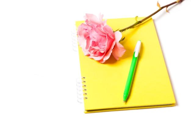 黄色のノートブックローズと白い背景の上のペン