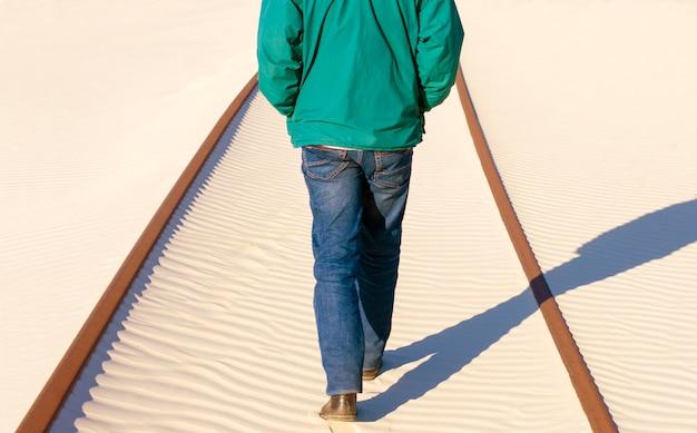 男は砂の中の鉄道の上に立つ