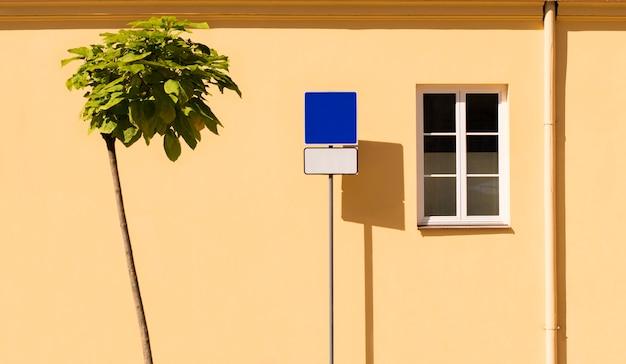 黄色の壁に木と道路標識
