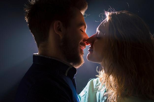 Портретное фото сексуальной молодой пары в пред поцелуе в потоках света
