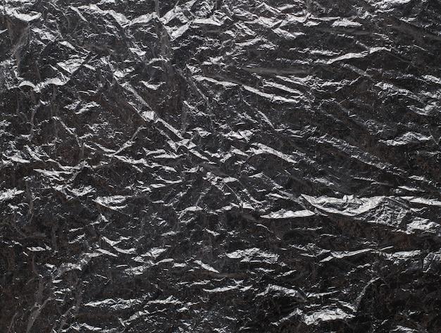 Мятая черная полиэтиленовая текстура с ярким фоном