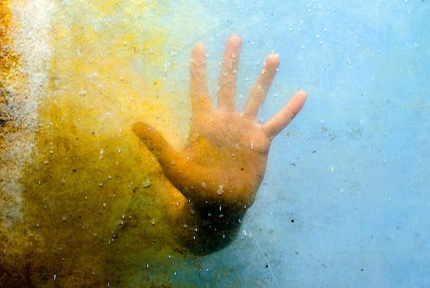 汚れた織り目加工ガラスの背後にある感情的な手