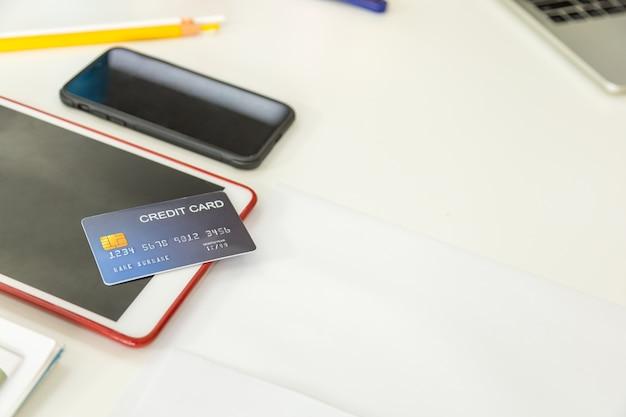 机の上のノートパソコンとコンピューターのタブレットとスマートフォンのモックアップ偽のクレジットカード