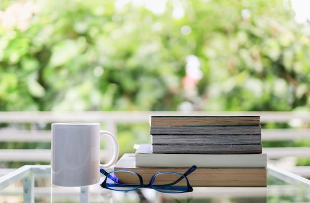教育とリラクゼーションのコンセプトです。ホットコーヒー、老眼鏡、緑豊かなガーデンビューのガラステーブルの上の本の白いマグカップのクローズアップ