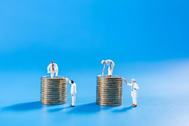 ビジネス、お金、計画および保存の概念。労働者のグループのクローズアップを洗浄し、金のスタックをペイント