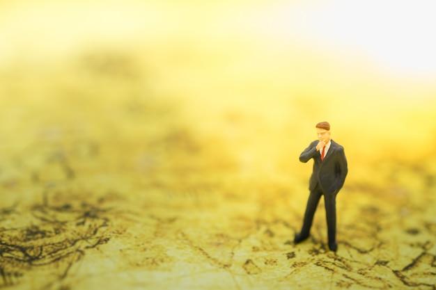 Бизнесмен миниатюрные люди фигура стоя и думая на карте мира.