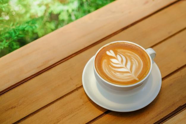 緑の自然とミルク泡ハート形アートとホットコーヒーカフェラテの白いカップ。