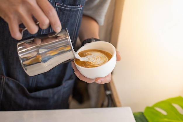 ラテアートを作成するためにホットコーヒーの白いカップにストリーミングミルクを注ぐバリスタ手のクローズアップ。