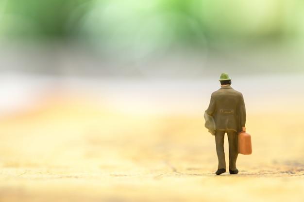 世界地図の上を歩く手荷物を持ったビジネスマンミニチュアフィギュア