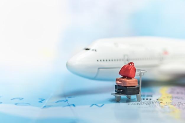 世界地図上のスーツケースとミニ飛行機モデルの近くにミニチュア空港荷物用トロリー。