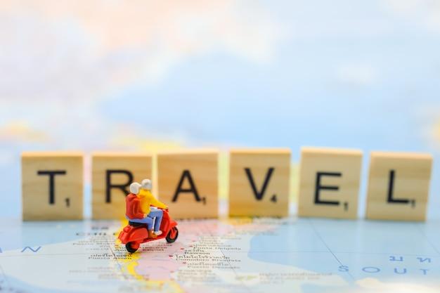旅行者のミニチュアフィギュアのグループは、木製のブロック文字おもちゃで世界地図にスクーターに乗る。