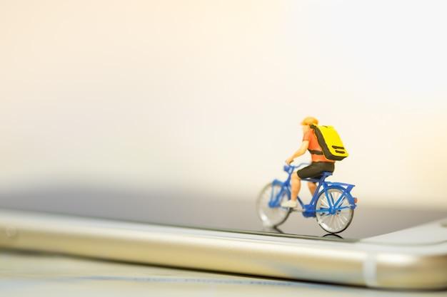 ミニチュアフィギュア男はスマートフォンでバックパックと自転車に乗る。