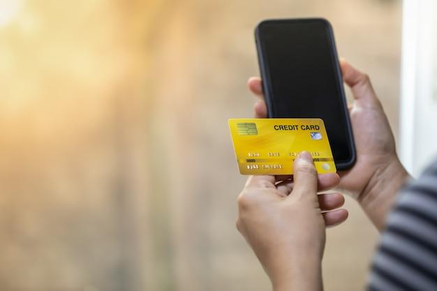 コピースペースを持つクレジットカードとスマート携帯電話を持つ女性の手。
