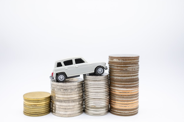 Белый мини игрушечный автомобиль на вершине стека монет на белом.