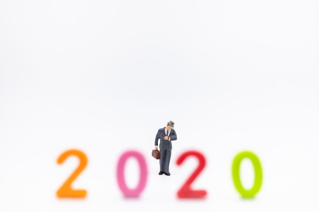 Бизнесмен миниатюрная фигура людей с чемоданом стоит и смотрит на наручные часы