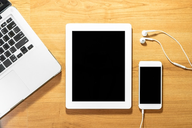 木製テーブルの上のスマートフォン、ラップトップ、タブレット、イヤホンの平面図