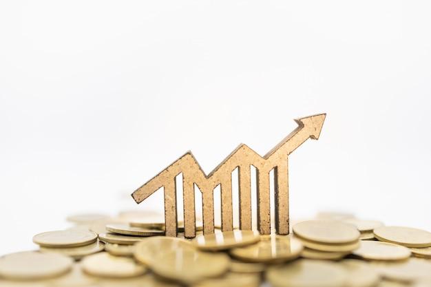 ゴールドコインの山の上の矢印アイコンと木製グラフの成長。