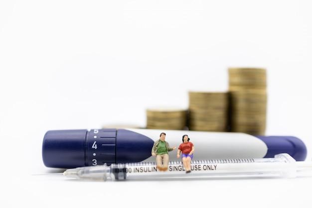 ゴールドコインのスタックとランセットでインスリン注射器に座っている男と女のミニチュアフィギュア。