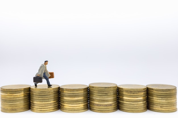 ビジネス、お金、金融、管理。ゴールドコインのスタックの行の上で実行されている実業家ミニチュアフィギュア。