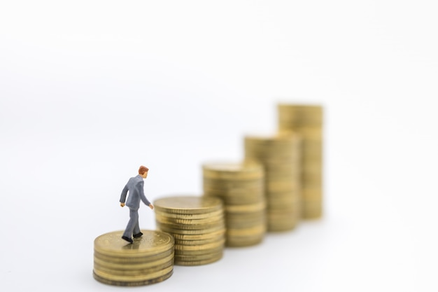 ビジネス、お金、金融、管理の概念。ゴールドコインのスタックの上を歩くビジネスマンミニチュアフィギュアのクローズアップ。